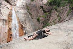 Het mooie vrouw liggen op de rots en heeft een rust op berg Stock Afbeelding