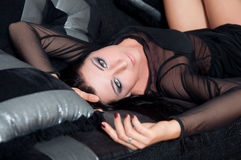 Het mooie vrouw model liggen in zwart kledingsbinnenland Royalty-vrije Stock Foto