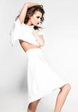 Het mooie vrouw model stellen in witte kleding in de studio stock foto