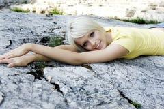 Het mooie vrouw ontspannen die op een rots liggen Stock Foto's