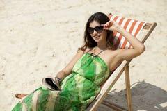 Het mooie vrouw ontspannen die op een zonlanterfanter liggen Stock Foto's