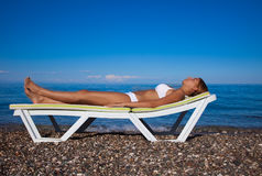 Het mooie vrouw ontspannen op het strand Stock Foto