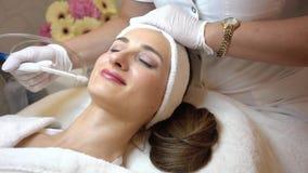 Het mooie vrouw ontspannen tijdens niet-invasieve gezichtsbehandeling voor verjonging stock video