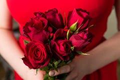 Het mooie vrouw rood houden nam boeket, de romantische verrassing van de Valentijnskaartendag toe royalty-vrije stock afbeeldingen