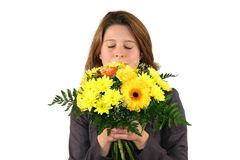 Het mooie vrouw ruiken bij een bos van bloemen Royalty-vrije Stock Fotografie