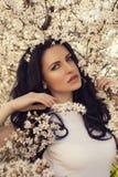het mooie vrouw stellen bij het park van de de lentebloesem Royalty-vrije Stock Foto's