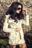 Het mooie vrouw stellen bij het park van de de lentebloesem Royalty-vrije Stock Afbeelding