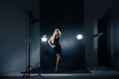Het mooie vrouw stellen bij studio in lichte flitsen Stock Afbeelding