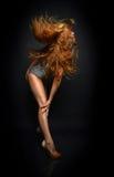 Het mooie vrouw stellen die in toevallige doek met winderig haar danst Stock Fotografie