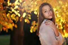 Het mooie vrouw stellen met de herfstbladeren Stock Foto's