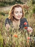 Het mooie vrouw stellen op het gebied van papaverbloemen, schoonheid, vormt a Stock Fotografie