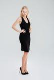Het mooie vrouw stellen in zwarte kleding met handen op heupen stock afbeelding
