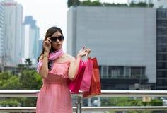 Het mooie vrouw winkelen binnen pingelt kleding die zonnebril met s dragen royalty-vrije stock foto's