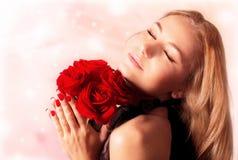 Het mooie vrouwelijke boeket van holdings rode rozen Stock Foto's