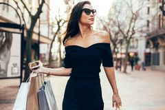 Het mooie vrouwelijke lopen op de straat met het winkelen zakken royalty-vrije stock foto's