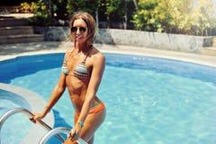 Het mooie vrouwelijke model stellen door de pool, openluchtportret Stock Afbeelding
