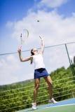 Het mooie vrouwelijke tennisspeler dienen Stock Afbeeldingen