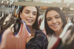Het mooie vrouwen genieten die voor kleren samen winkelen stock afbeelding