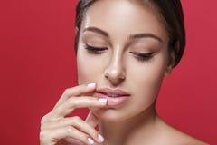 Het mooie vrouwengezicht wat betreft haar lippen door vingers sluit omhoog studioportret op rood Royalty-vrije Stock Afbeelding