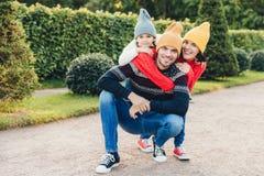 Het mooie wijfje, meisje omhelst hun knappe vader en de echtgenoot, heeft goede verhouding, heeft actieve levensstijl, opnieuw st stock fotografie