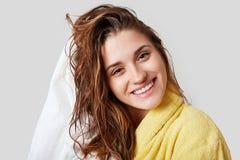 Het mooie wijfje met nat haar, neemt douche, droogt hoofd met handdoek, die tevreden na het nemen van bad, gekleed in gele badjas royalty-vrije stock afbeeldingen