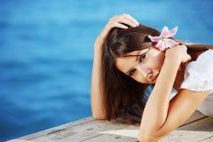 Het mooie wijfje van de zomer met bloem in haar haar Royalty-vrije Stock Afbeelding