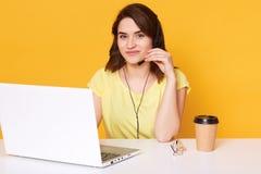 Het mooie wijfje zit bij wit bureau met geopende laptop computer, schrijft e-mail, gebruikt snelle internetdiensten, stelt geïsol stock afbeelding