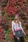 Het mooie zoete meisje in een baret en een rok loopt onder de heldere rode kleur van bladeren in de heldere zonnige dag van het d stock fotografie
