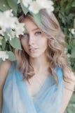 Het mooie zoete tedere meisje met blauwe ogen in een blauwe kleding met licht die haar in jasmijn is vastgelopen bloeit royalty-vrije stock afbeelding