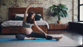 Het mooie zwangere meisje rekt lichaam en benen uit die op yogamat zitten en vooruit met opgeheven hand buigen De zolder van Nice stock videobeelden