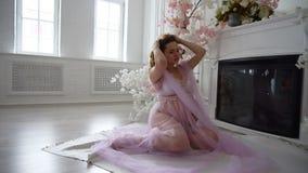 Het mooie zwangere meisje zit op vloer dichtbij de open haard stock videobeelden