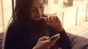 Het mooie zwart-haired meisje bekijkt de telefoon en het glimlachen stock videobeelden