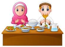 Het moslimpaar bidt samen vóór onderbreking het vasten stock illustratie
