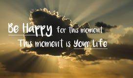 Het motievencitaat 'gelukkig is voor dit ogenblik Dit ogenblik is uw leven 'op een achtergrond met wolk en stralen van zonlicht v stock fotografie