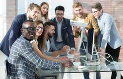 Het multi-etnische commerciële team bespreekt de resultaten van zijn werk royalty-vrije stock afbeelding