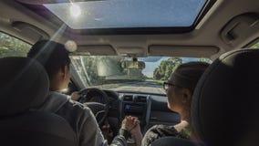 Het multi-etnische paar berijden in een auto, een man die de hand van een vrouw houden stock afbeeldingen
