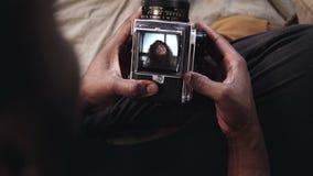 Het multi-etnische paar heeft een photoshoot Mening van jonge vrouw in videorecorder van oude be*wegen-filmcamera De mens neemt e stock foto