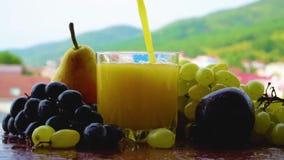 Het Multifruitsap wordt gegoten in een wijnglas stock footage