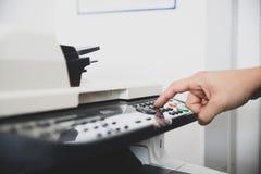 Het multifunctionele apparaat in bureaucentrum, arbeider plaatst de aftastenopties voor verzendt digitaal exemplaar van documente royalty-vrije stock afbeeldingen