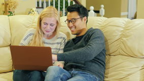 Het multinationale paar thuis ontspannen die, op laag, laptop gebruik zitten stock video