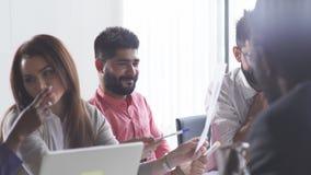 Het multiraciale bedrijfsmedewerkers spreken, die op werkplaatsen op elkaar inwerken stock footage
