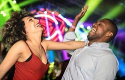 Het multiraciale jonge paar die bij nachtclub dansen met laserlicht toont Royalty-vrije Stock Afbeeldingen