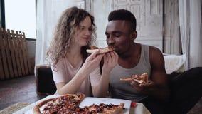 Het multiraciale paar heeft pret tijdens de maaltijd Vrouwenvoer de man een plak van pizza Mannetje en wijfje die snel voedsel et stock footage