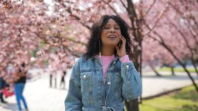 Het multiraciale vrouw luisteren aan muziek in een park, kers komt rond tot bloei boom stock videobeelden