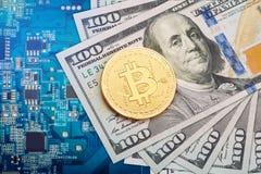 Het muntstuk van bitcoin ligt op dollars tegen de achtergrond van de videokaart Stock Foto