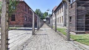 Het Museum van het Auschwitzconcentratiekamp - Omheiningen en Prikkeldraad tussen de barakken 7 juli, 2015 stock afbeeldingen