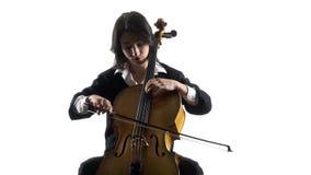 Het musicusmeisje speelt een violoncel repeterend een samenstelling Witte achtergrond stock videobeelden