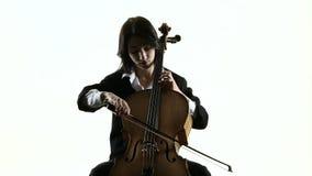 Het musicusmeisje speelt een violoncel repeterend een samenstelling Witte achtergrond Langzame Motie stock videobeelden