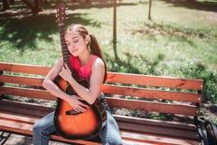 Het musicusmeisje zit op bank en houdt gitaar Zij leunt aan het Het meisje heeft haar ogen en genieten van gesloten royalty-vrije stock foto
