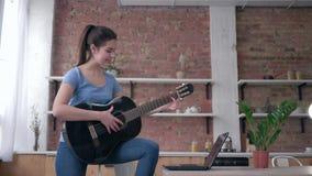Het muzikale onderwijs, gelukkig mooi gitaristmeisje het leren spel stringed muzikale laptop van het instrumentengebruik computer stock videobeelden